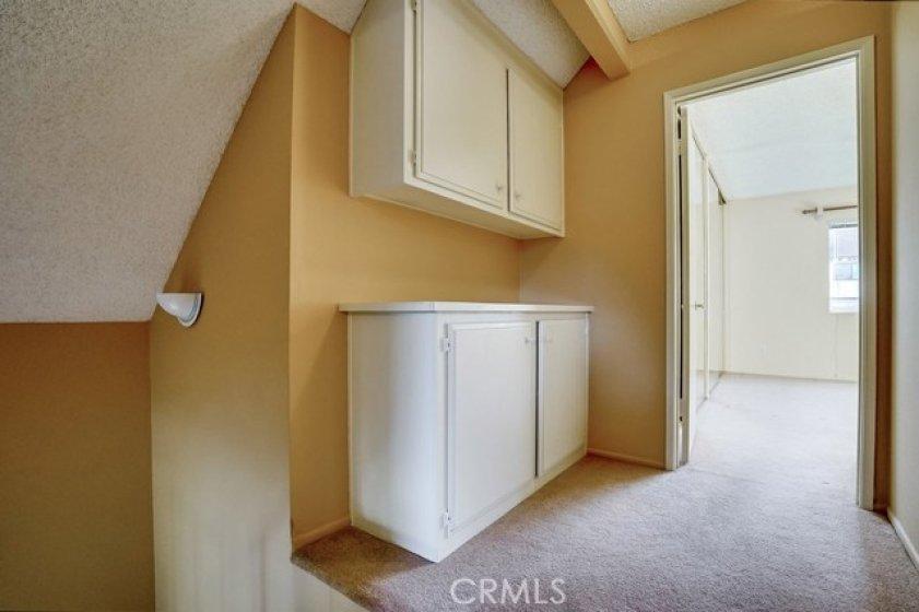 Upper hallway offers built-in linen cabinets