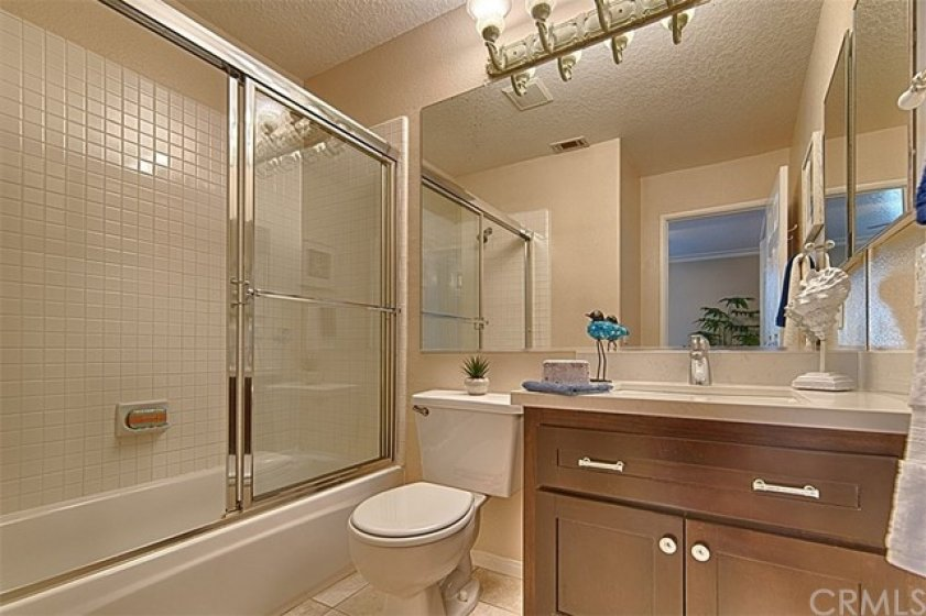 Upstairs full bath with quartz counter top & rich brown cabinet.