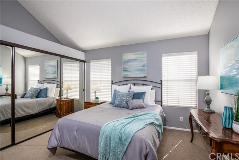 The large secondary bedroom, with 3 large mirrored closet doors, vaulted ceilings and plenty of natural light.