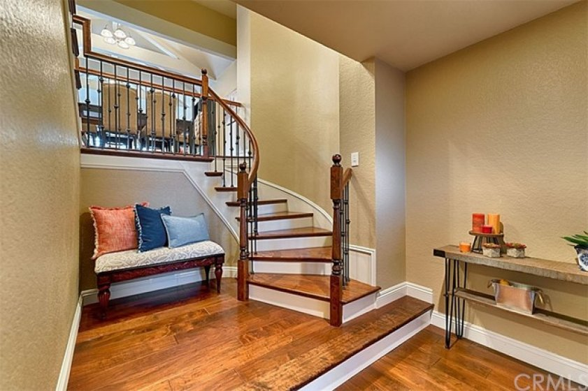 Open the front door to custom staircase, wood floors in this bright floor plan.