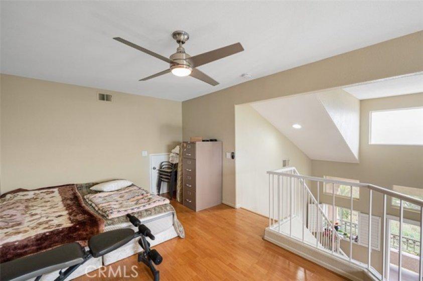 Ceiling fan and wood laminate flooring in loft.