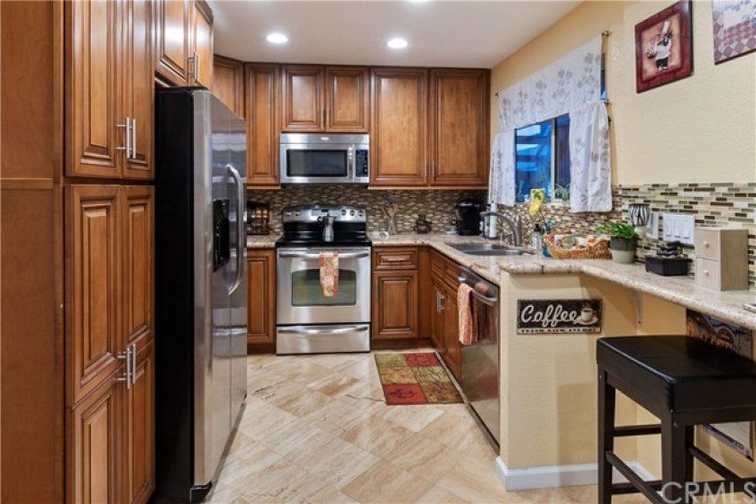 Remodeled kitchen, solid surface counters, high end materials, stainless steel appliances and stone flooring