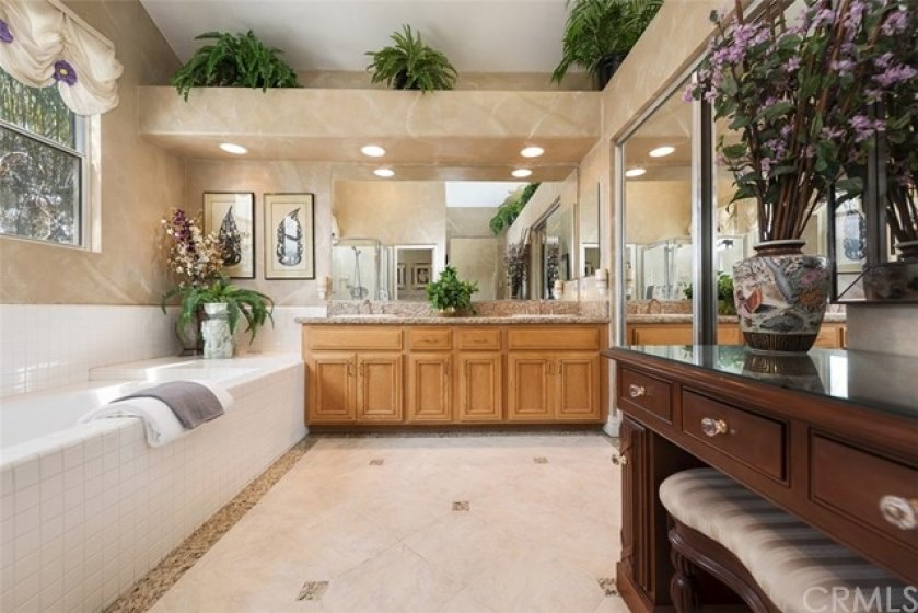 Another view of master bath with dual sinks and walk-in closet with mirrored doors