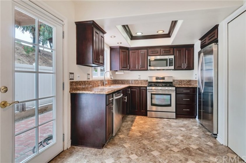 Upgrade kitchen with tile flooring, granite counter tops and stainless steel appliances.  French door to the big Patio.