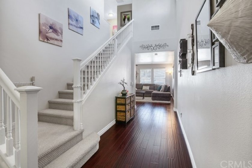 Hallway leading to living room, dining room and kitchen.  Stairs leading up to two bedrooms and two bathrooms.