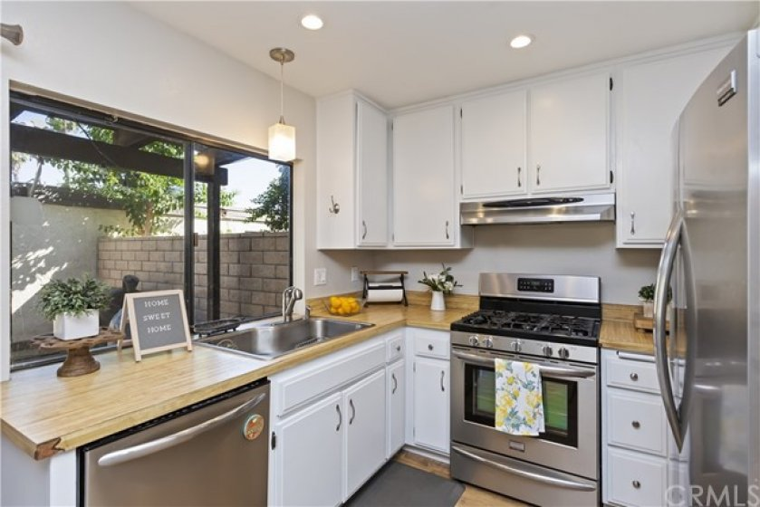 Kitchen with white cabinets and stainless steel appliances.  Check out the views into your backyard!