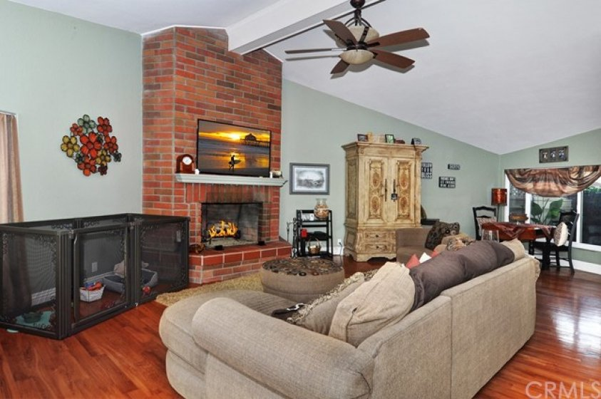 Living Room with fire place, hardwood flooring and vaulted ceiling