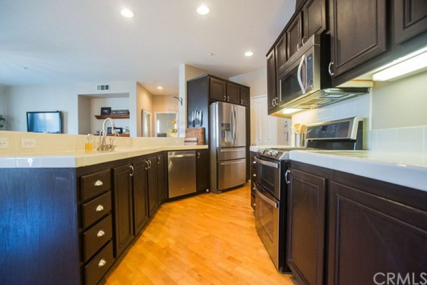 The kitchen has beautiful cabinetry, tile counters, stainless steel appliances and a walk in pantry.