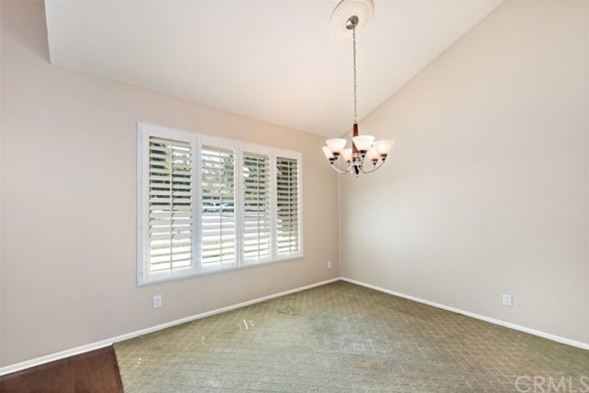The formal dining room also is accented with plantation shutters and a lovely chandelier.
