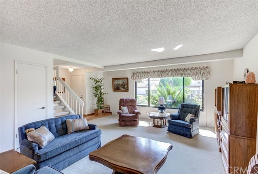 Photo from Dining area shows large living room, front door and staircase.