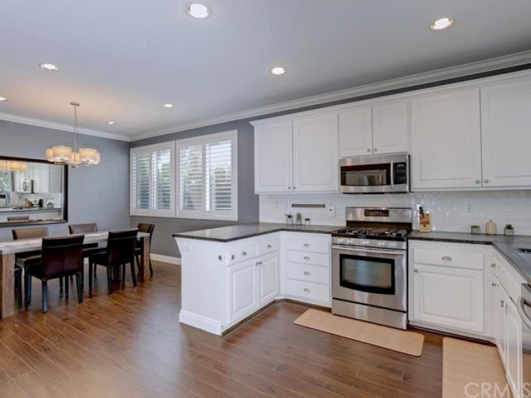 The upgraded kitchen opens to all of the living areas of the home and includes stainless steel appliances, subway tile, custom white cabinets and pulls, and recessed lighting.