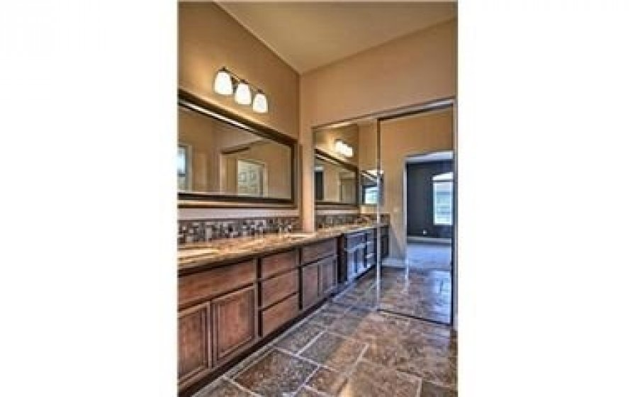 Master bath has granite countertops with dual sinks and travertine floors. Upgraded hardware and lighting fixtures.