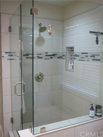Large walk in shower with beautiful seamless glass doors, extra large tiles and stone pebble flooring.