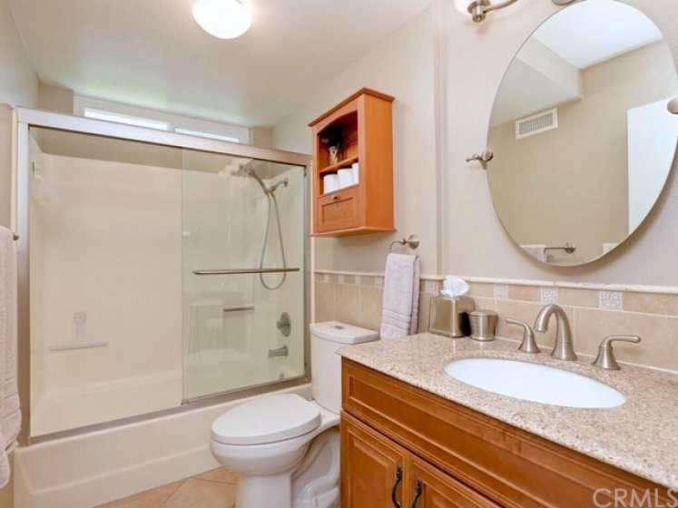 The full bath upstairs has updated cabinets, granite counters, tile floors, and custom lighting, mirrors, and backsplash.