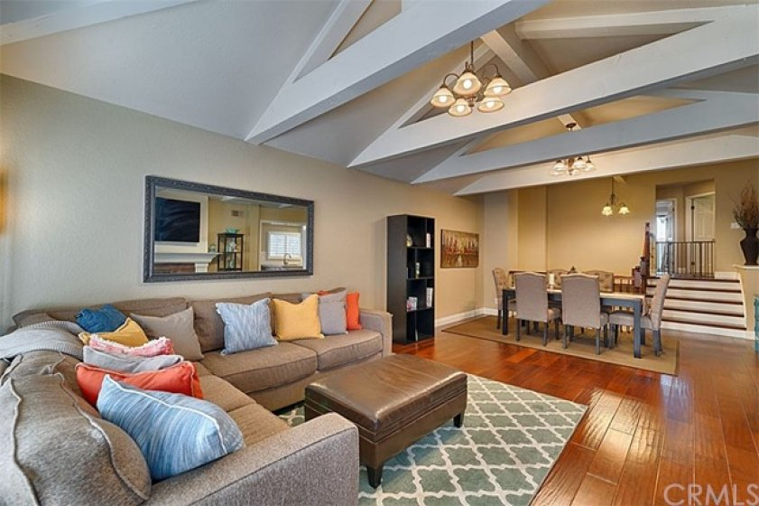 Living room from back doors.  New flooring, paint, and baseboards in a generous space.