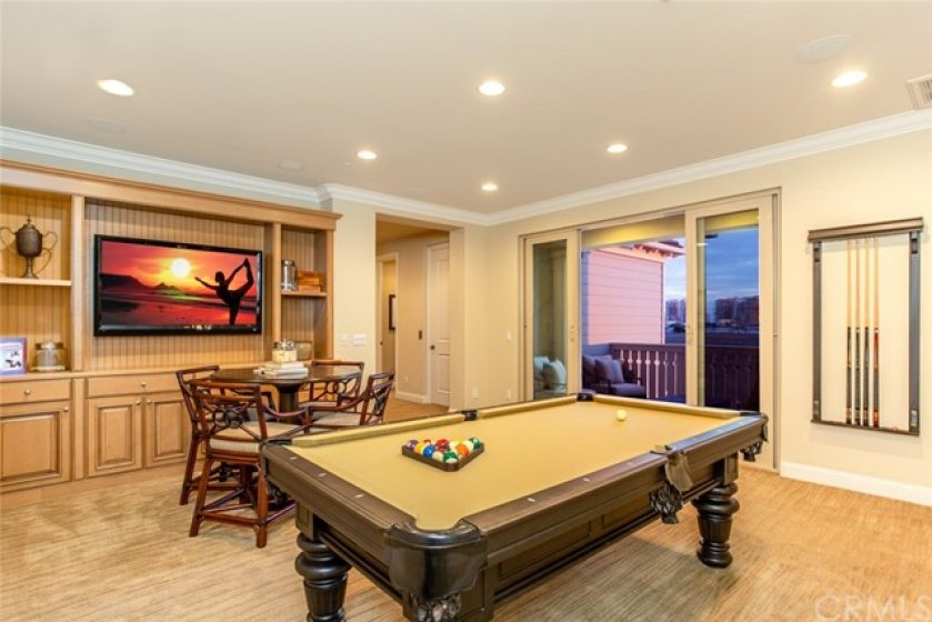 Second floor family game room with glass sliding doors leading to private balcony.