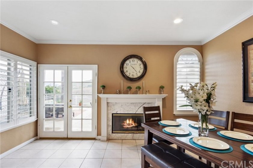 The dining room has a cozy fireplace with a custom wood mantle. The double french doors lead to the private backyard.