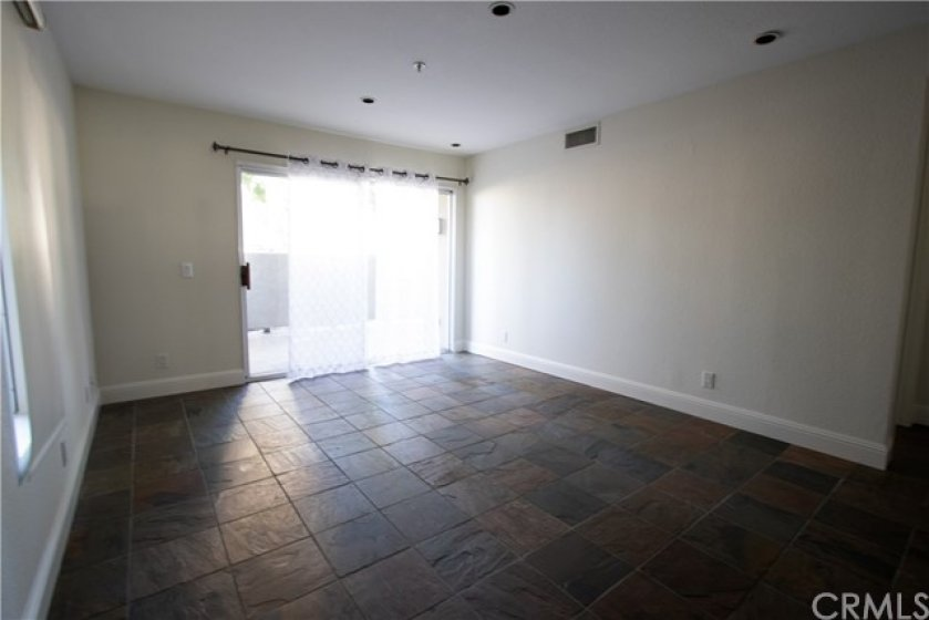 generous living area with stone tile floor opening to patio