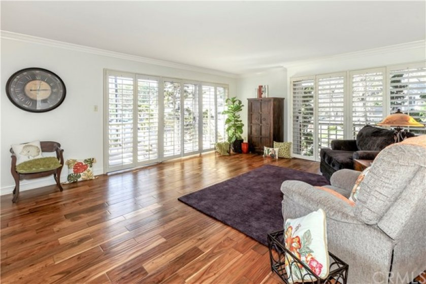 Wood flooring throughout. Living area with plantation shutters south and west facing sliding windows to narrow balcony areas.
