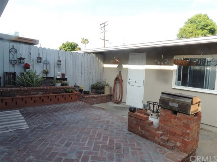 Large outdoor patio with planter bed, built-in barbeque and direct acccess to the two car garage