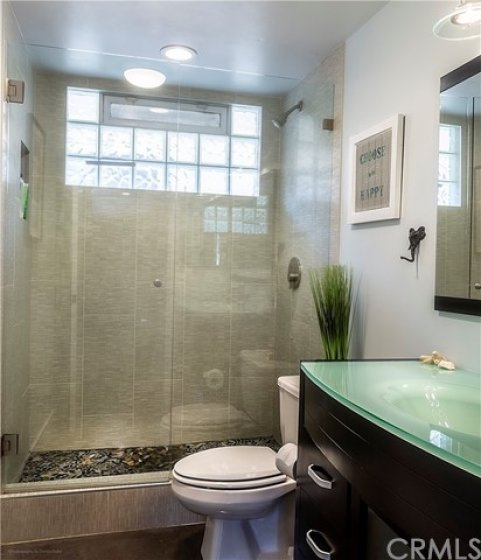 Bathroom is well designed with an exquisite stone floor and well designed practical window to let in and open to let moisture out. The glass counter flows right into the sink.