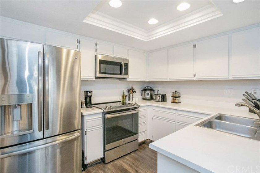 Bright kitchen with recessed lighting, stainless steel appliances and painted cabinets.