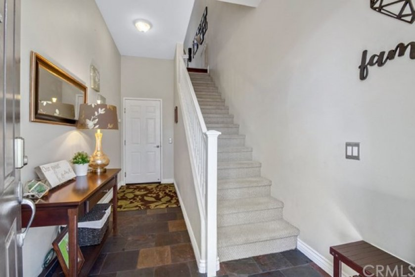 Entryway with door leading to tandem, two car garage.  Stairs leading to living space.