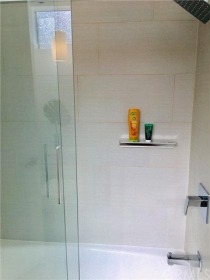2nd suite's bathroom with new tiling and top of the line fixtures, and sliding glass doors.