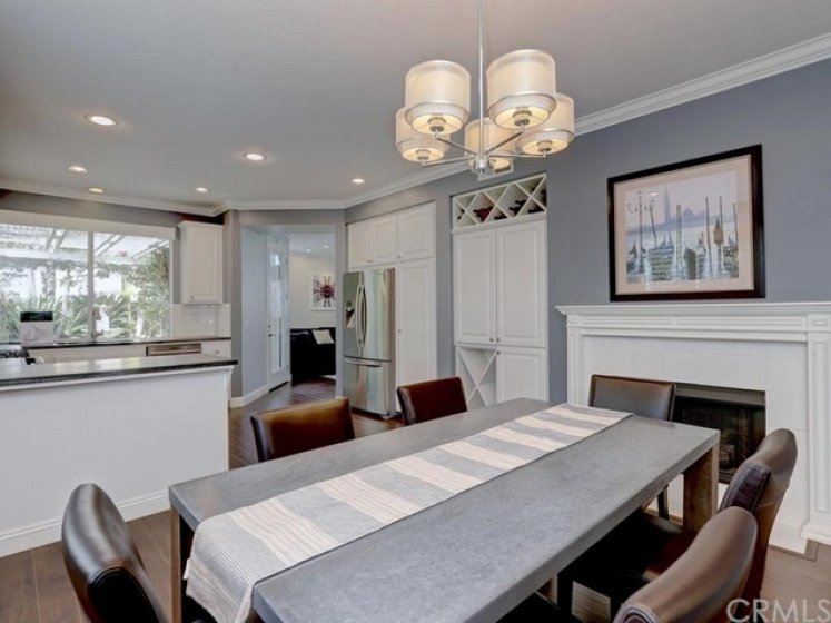 Reverse angle from the current dining room to kitchen showing the breakfast counter at the kitchen counter and the custom fireplace mantle and white cabinetry.