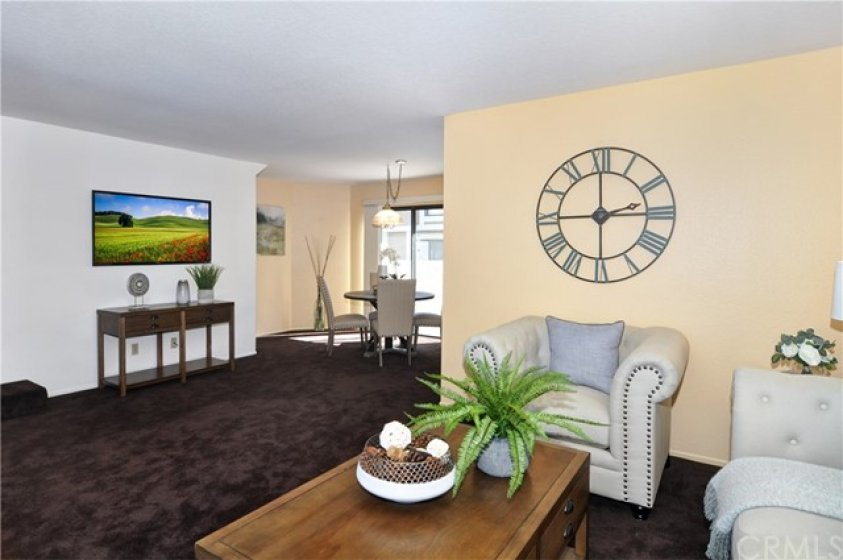Spacious and open living area with dining room and sliding doorway to rear balcony
