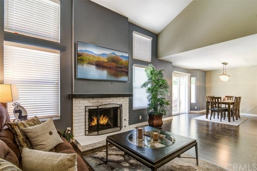 OPEN FLOORPLAN - Warm inviting fireplace, flows into dining area