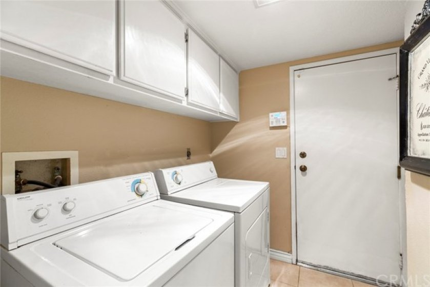Inside Laundry room with overhead cabinets- Gas and electric connections- Entry door from attached two car garage
