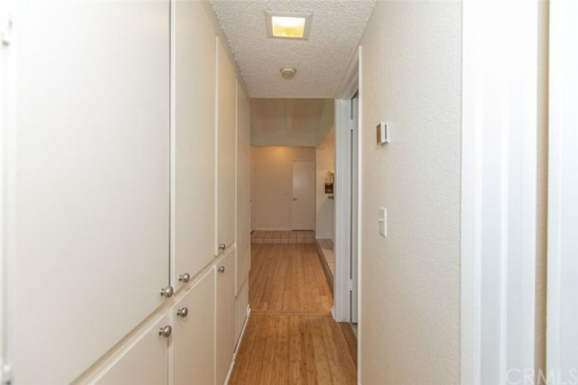 Hallway with lots of cabinetry.