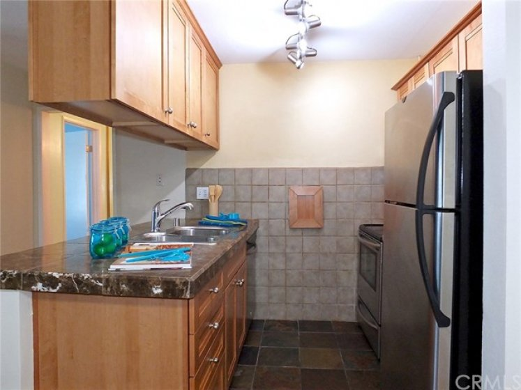 Tile floor and wall, stainless steel appliances