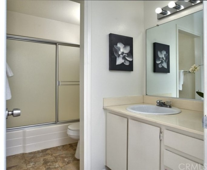 This full bath off the hallway services the 3 secondary bedrooms and has the vanity area separated by a privacy door from the tub/shower combo and commode.