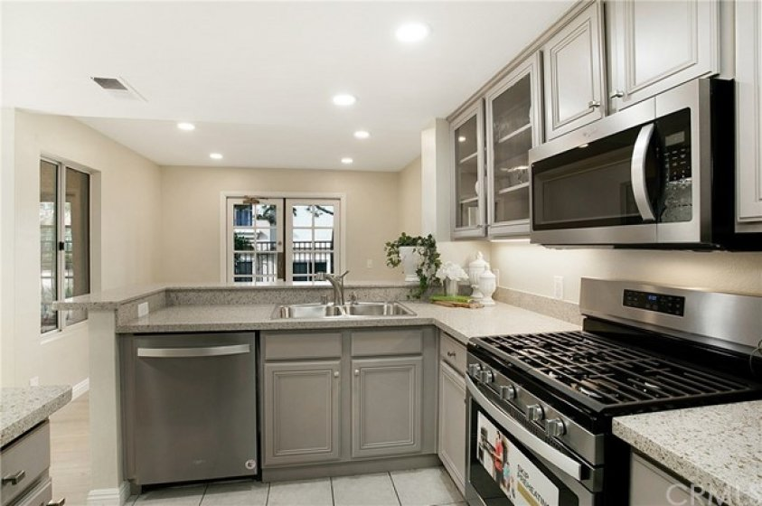 Remodeled kitchen with new custom cabinets and stainless appliances including fridge