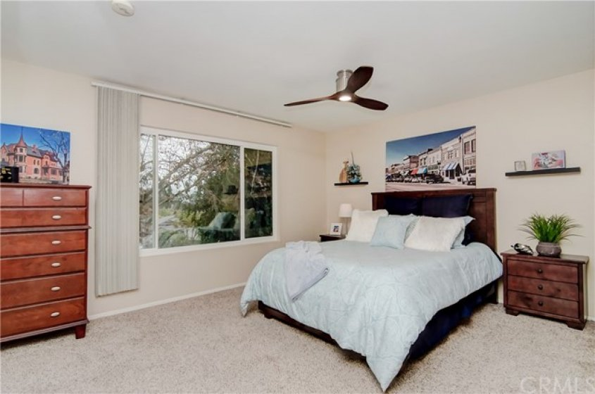 LARGE MASTER BEDROOM WITH CEILING FAN AND A VIEW.