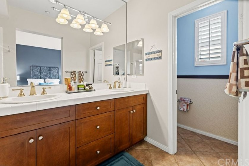 Master suite bath with large counter space, beautiful cabinets, dual sinks and private toilet area with door.