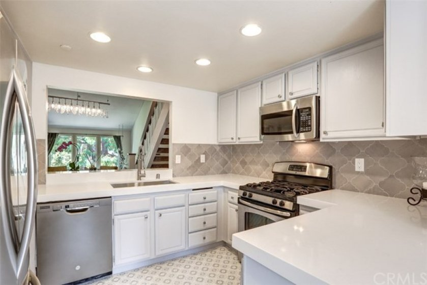 Tastefully updated kitchen with brand new counters, backsplash, sink/faucet, and flooring.