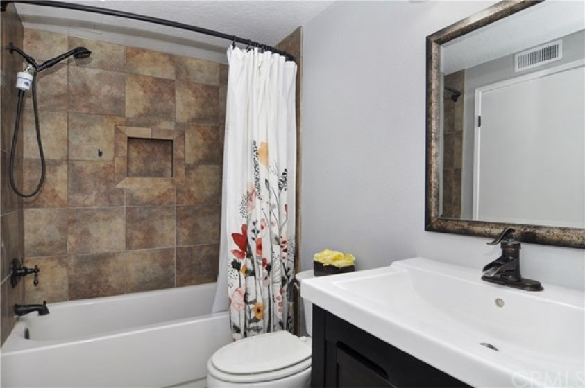 The bathroom includes a custom tiled shower area and upgraded vanity.