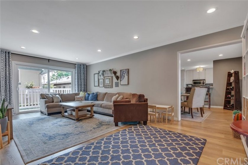 Spacious Living Room with Beautiful Wide Plank Wood Laminate Flooring and Recessed Lighting.