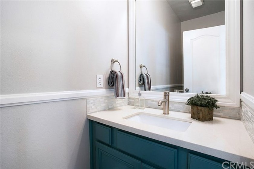Remodeled main floor bath with quartz counters and glass back splash
