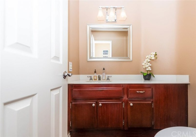 Downstairs half bath features upgraded lighting and rich wood cabinetry.
