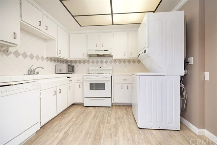 Spacious kitchen features, dishwasher, stackable washer, dryer. gas stove, tile flooring and ample counter top space, cabinets, and drawers