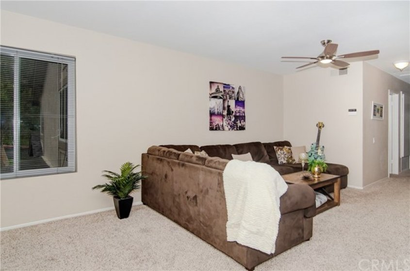MORE LIVING ROOM WITH CEILING FAN AND NEWER CARPET.