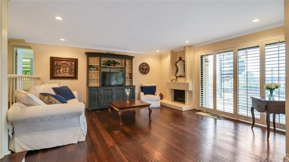 Spacious living room with lovely hard wood flooring and plantation shutters!