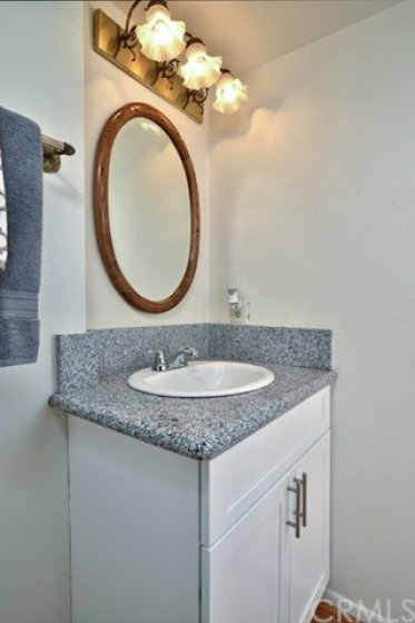 Just off the foyer is a convenient remodeled powder room with white shaker style vanity with granite counter top.