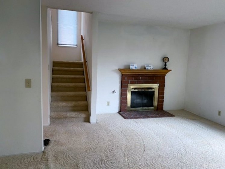 Gas burning fireplace for those chilly evenings and stairwell to upstairs bedrooms