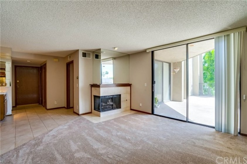 Living room with Entry door to the left, and sliding glass doors to the right opening to the large patio