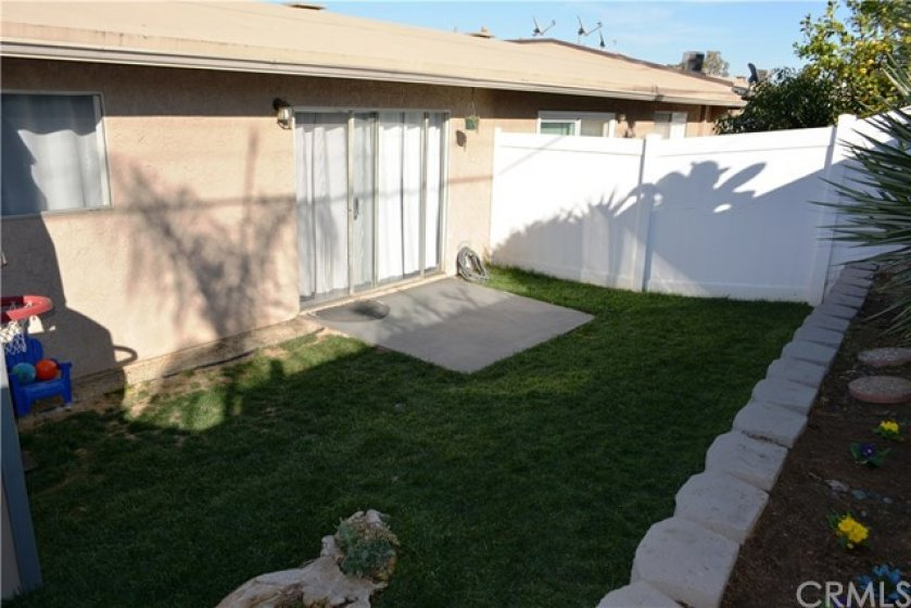 From this vantage point you can appreciate the spaciousness of this back yard and the privacy the newer vinyl fences offer; Truly a huge treat to have an actual back yard in a 1bd condo.